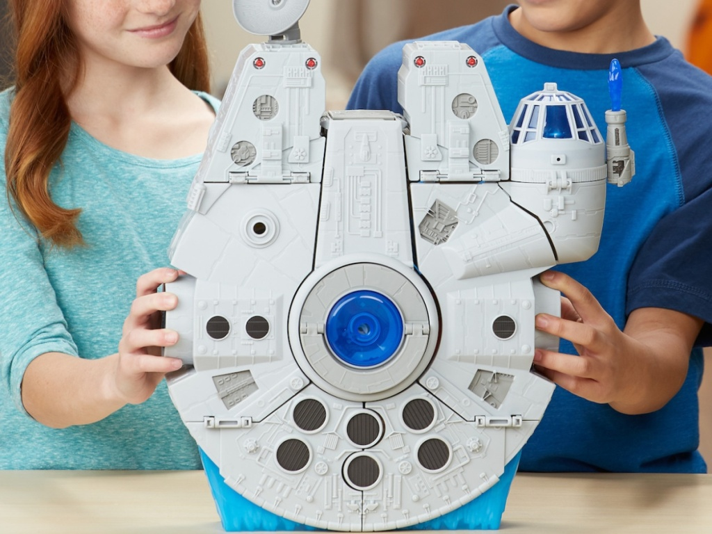 boy and girl playing with large toy space ship