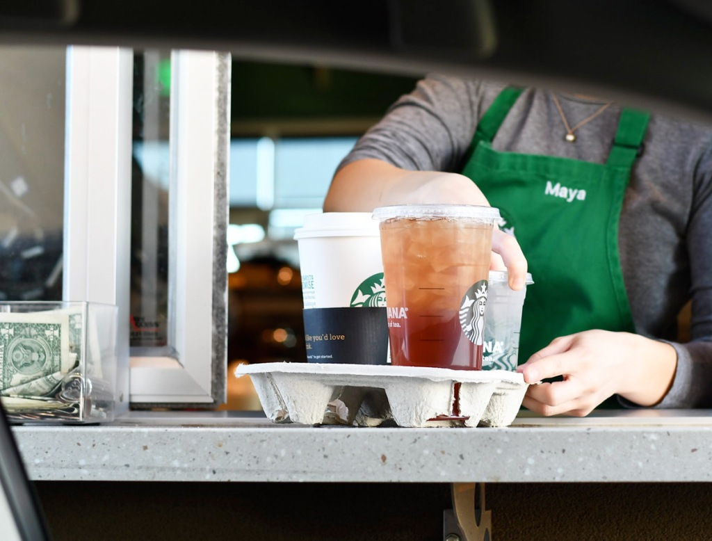 view of drive-thru window at starbucks with barista handing out drinks