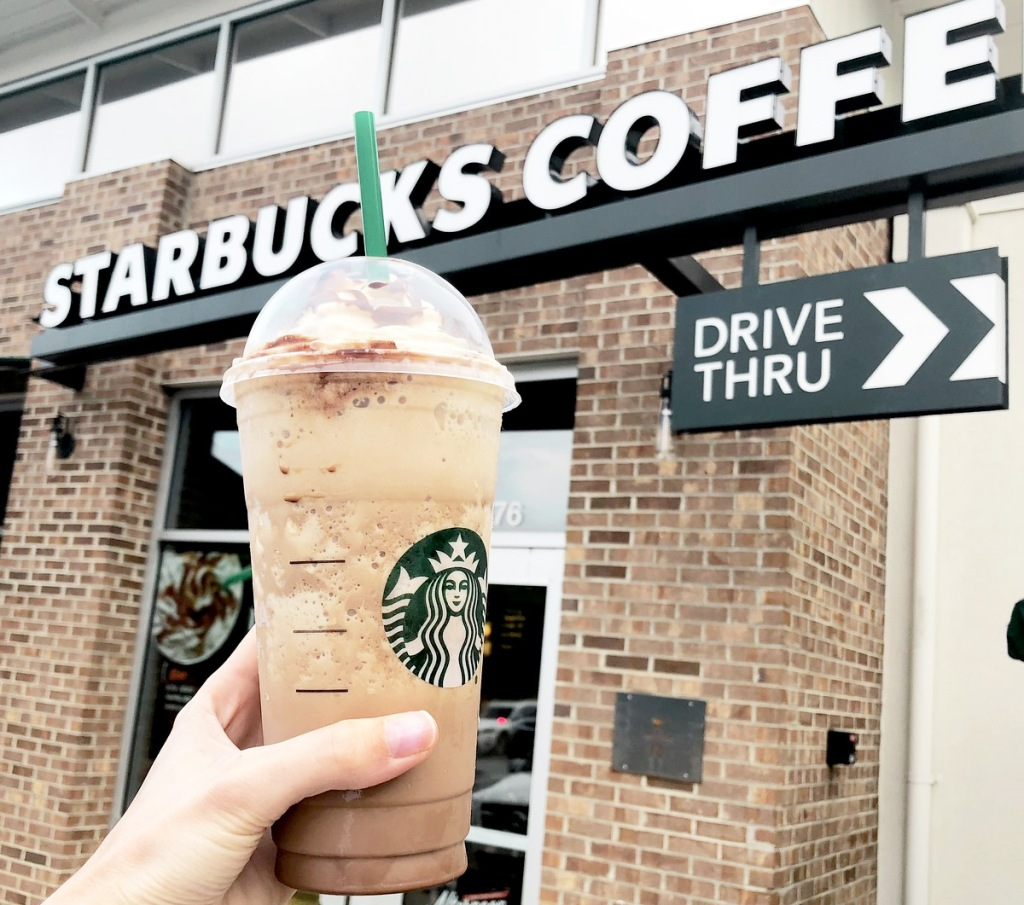 person holding up frappuccino drink in front os starbucks drive-thru sign
