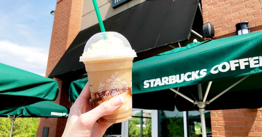person holding up frappuccino drink outside of starbucks store with green umbrella