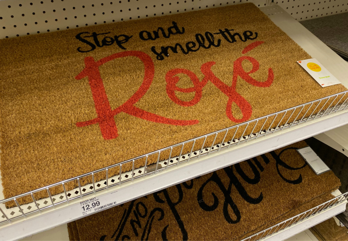 """brown coir mat on store shelf that says """"Stop and Smell the Rosé"""""""