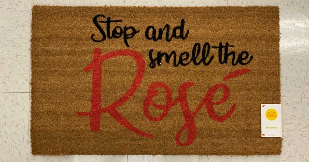 """brown coir mat on floor that says """"Stop and Smell the Rosé"""""""
