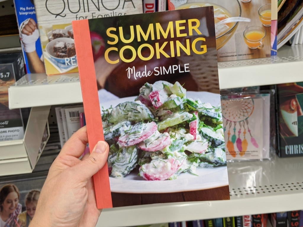 hand holding a Summer Cooking Made Simple cookbook