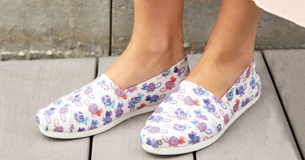 women wearing a pair of white slip-on TOMS shoes with red and blue rat print all over them
