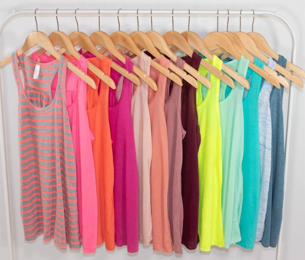 multiple tank tops in a wide variety of bright colors handing on wooden hangers