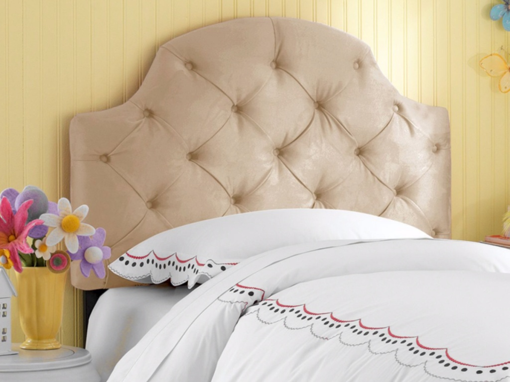 girls tufted headboard with a white blanket on the bed next to flowers