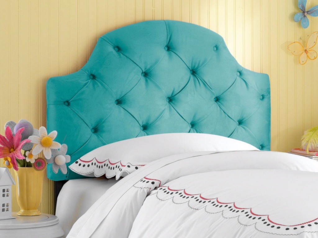 teal tufted headboard attached to a bedframe with a white blanket