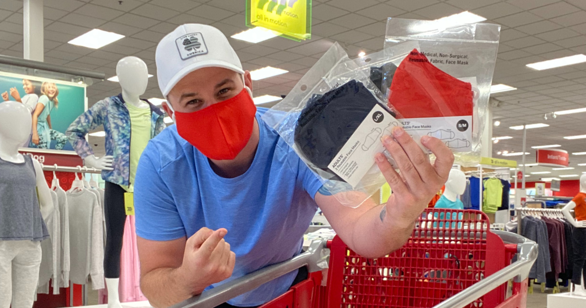 man holding black and red face masks at target by cart