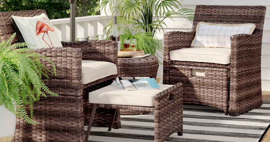 brown wicker patio set with two chairs, two ottomans and matching side table on a striped outdoor rug