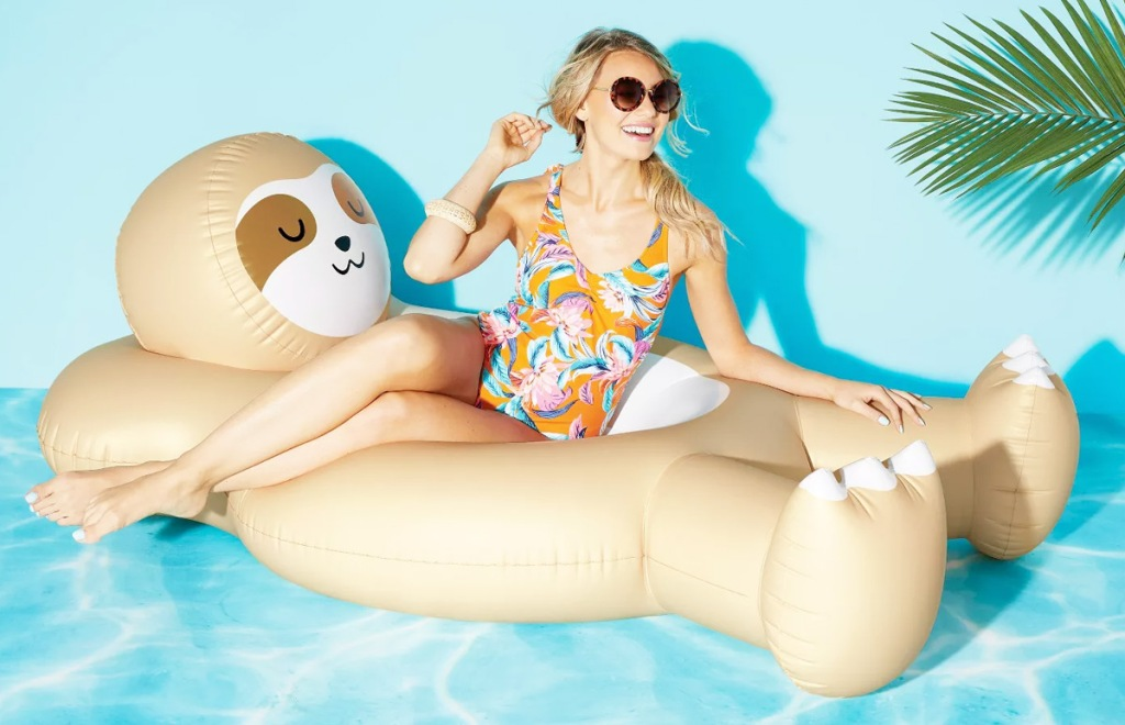 woman floating in water on a sloth shaped pool float