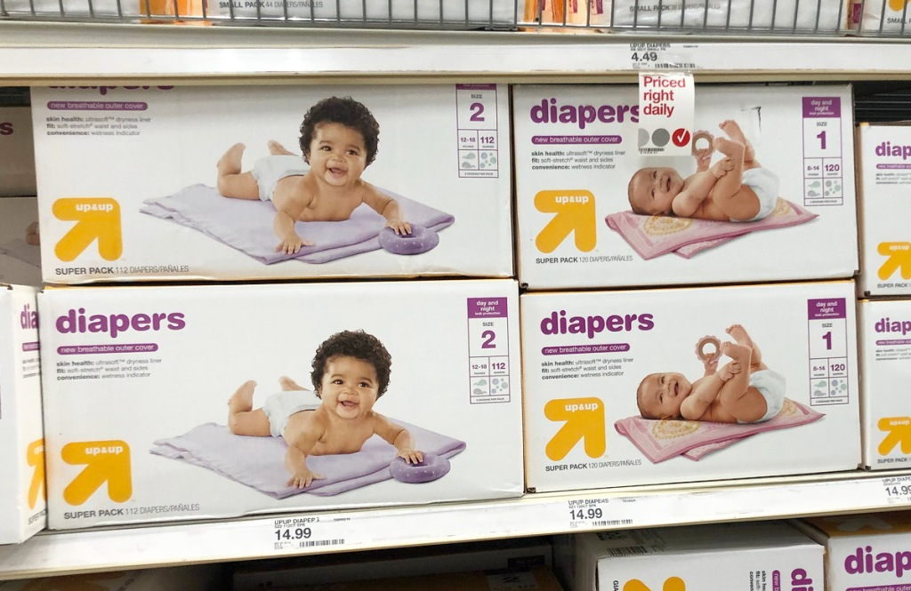 store display shelfs full of white and yellow boxes of up & up brand diapers