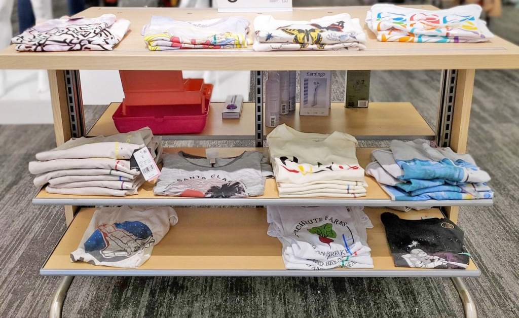store display shelves of various women's graphic tees