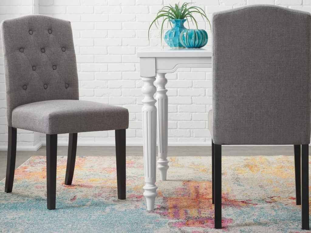 2 grey tufted dining chairs sitting next to a white table with a plant
