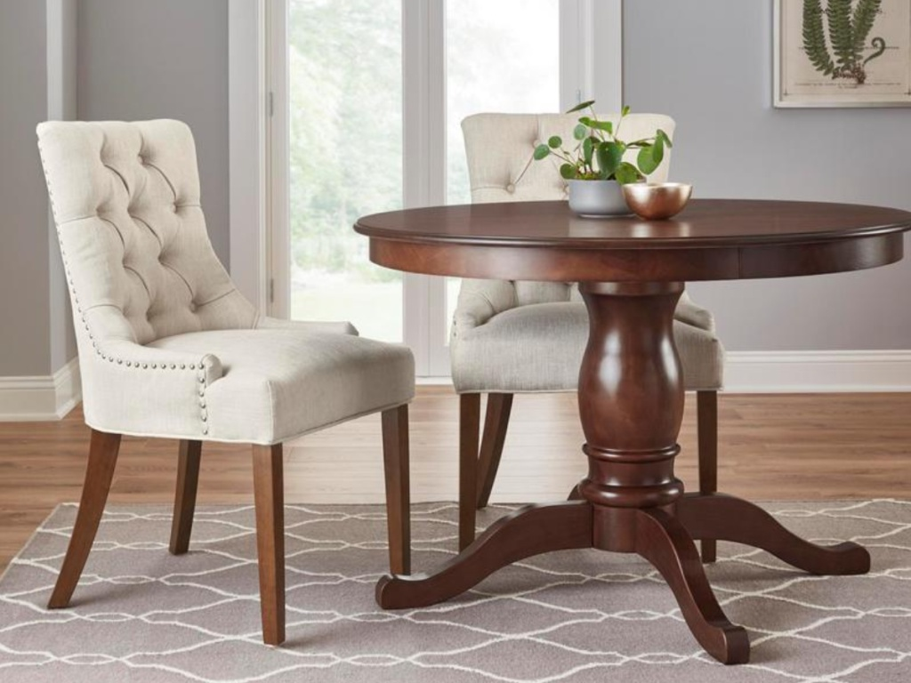 2 white tufted dining chairs next to a round brown kitchen table