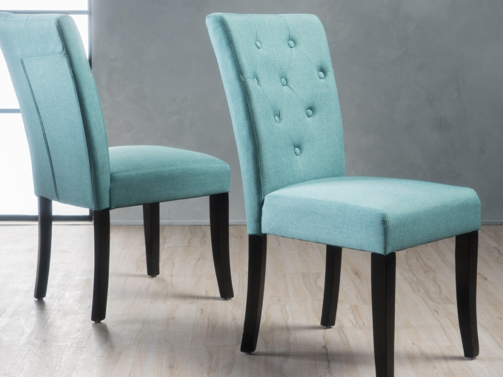 2 light blue tufted dining chairs facing away from each other
