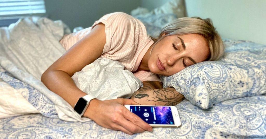 Woman falling asleep peacefully while listening to a sleep meditation