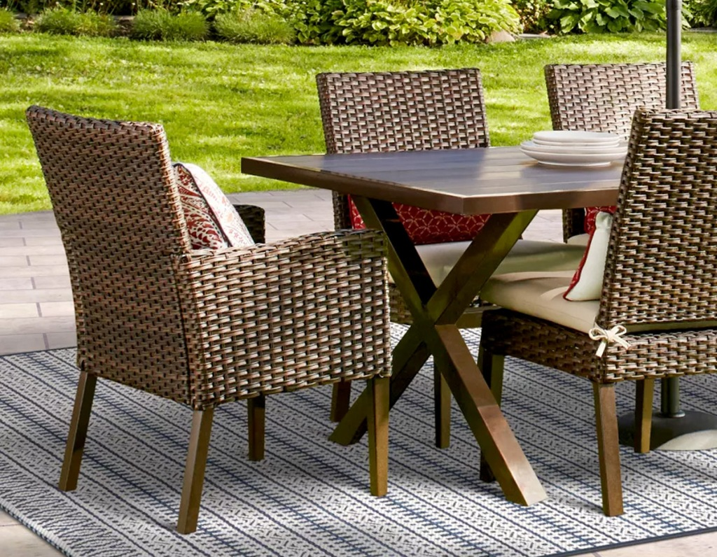 brown wicker patio chair at outdoor table on striped rug
