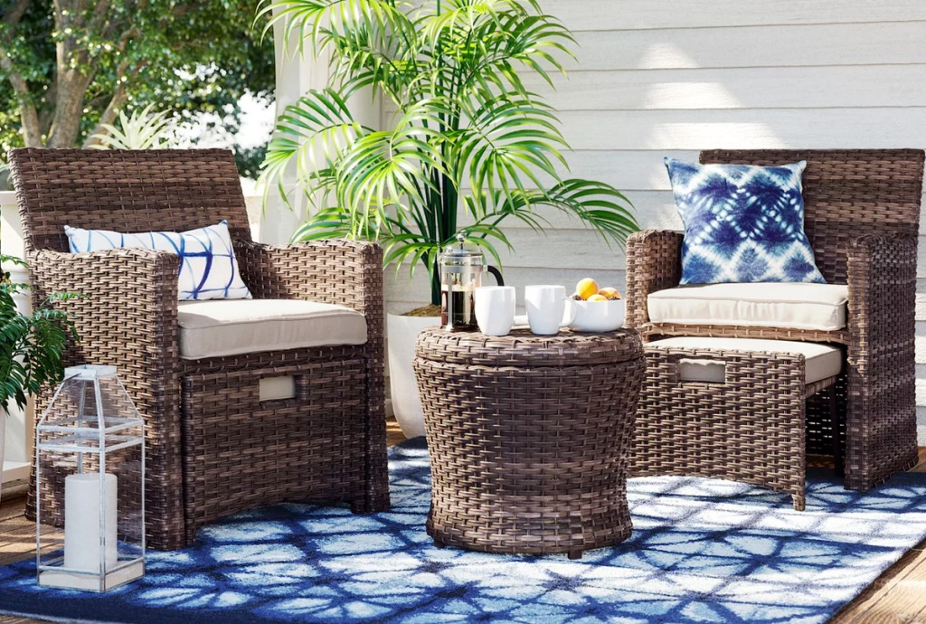 brown wicker patio set with two chairs, two ottomans and matching side table on a blue outdoor rug