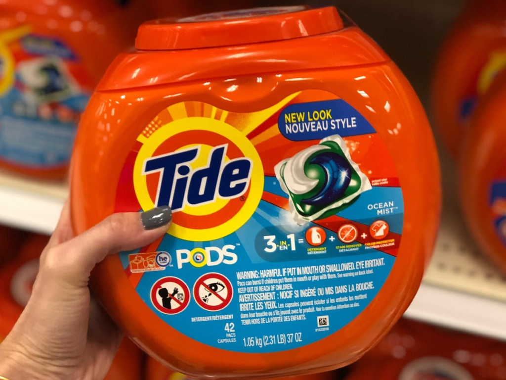 hand holding a large container of Tide Pods