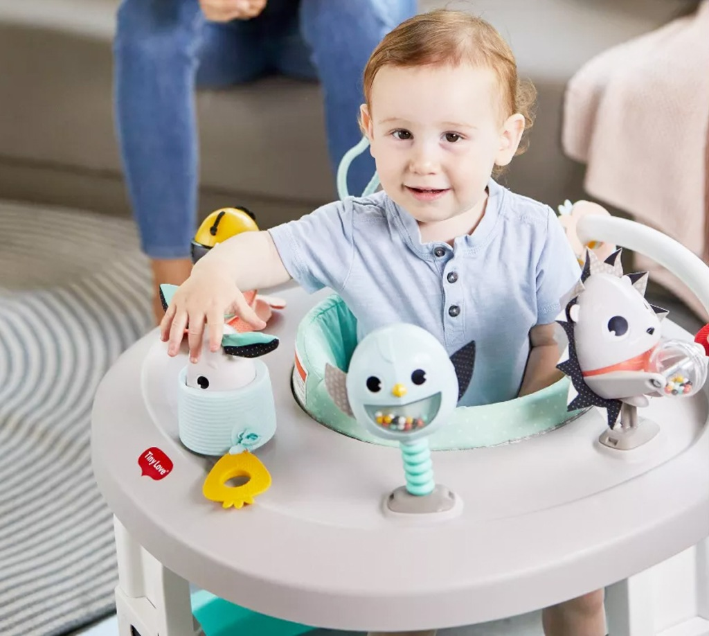 baby seating in grey rolling activity center with toys attached