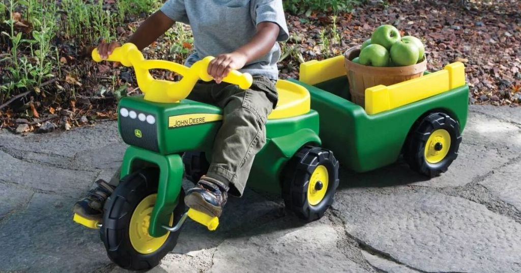 child on john deere rideon tractor toy with wagon in back carrying apples in a basket