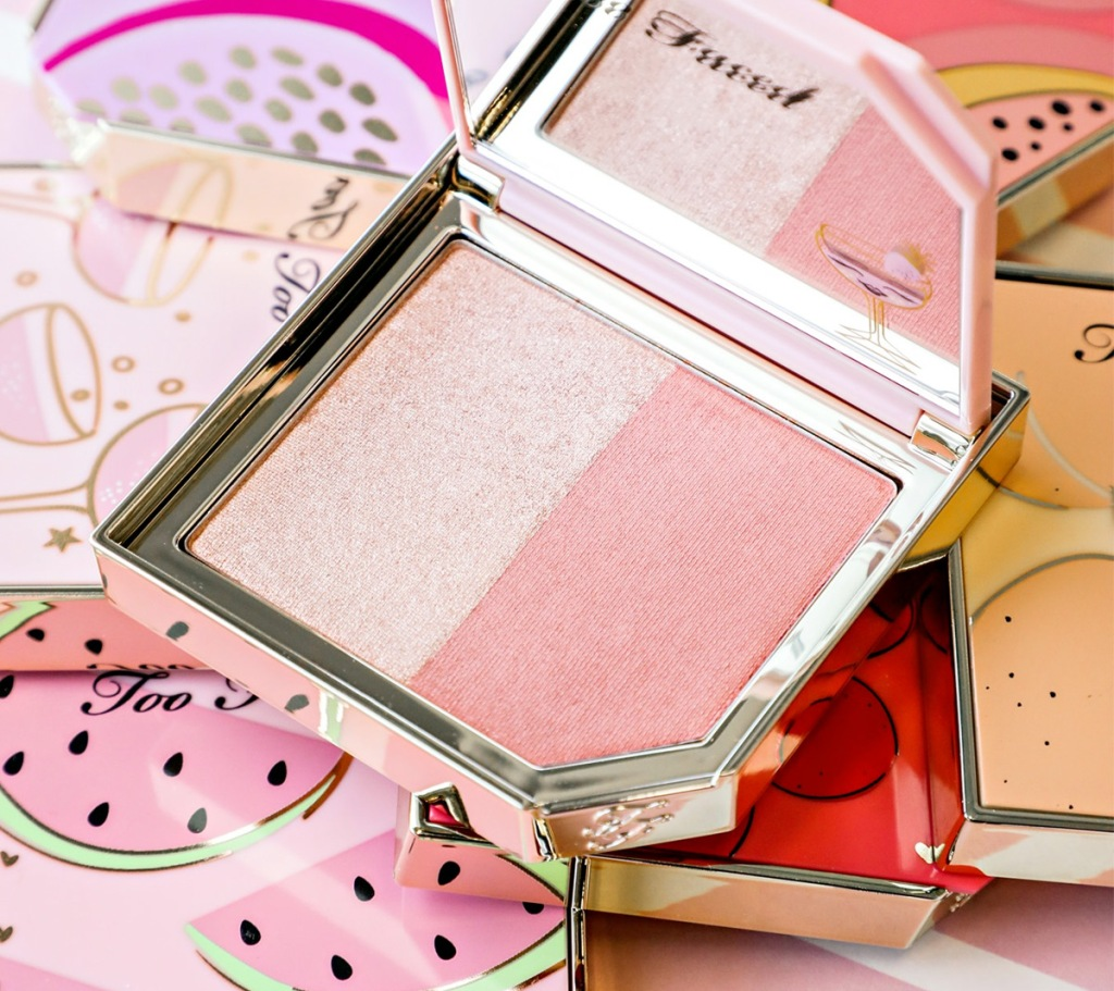 blush compact open on top of other compacts with fruit designs