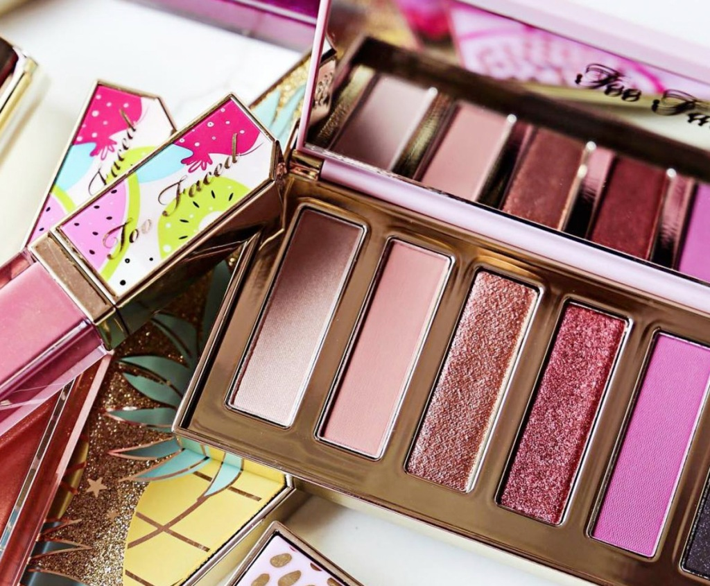 eyeshadow palette and lip glosses on top of other makeup items