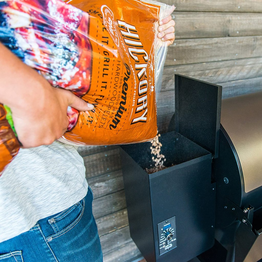 Man pouring Traeger Hickory Pellets from bag