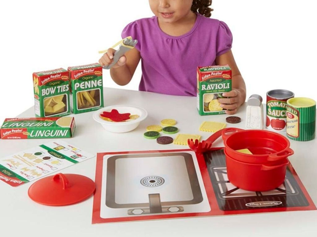 little girl playing with play pasta set