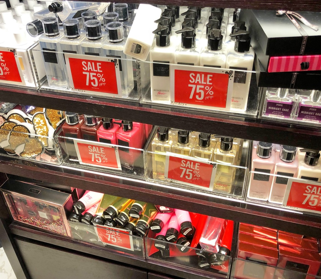 various different types of body lotions and sprays on store display shelfs with 75% off sale signs
