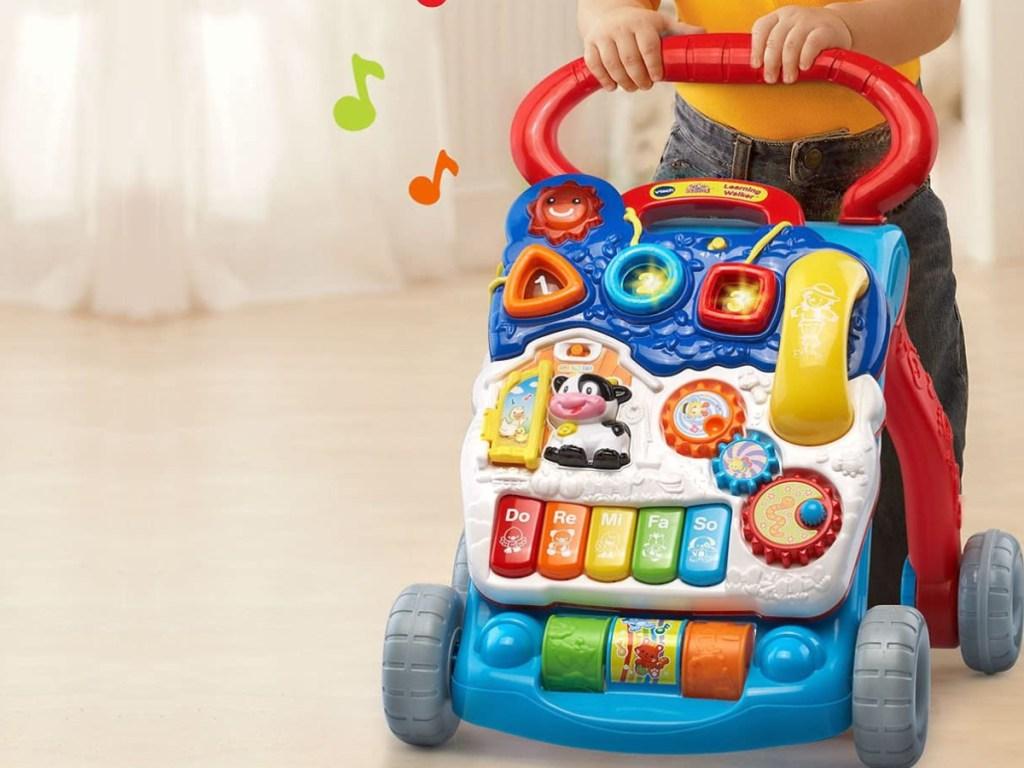 baby using toy walker on floor in home
