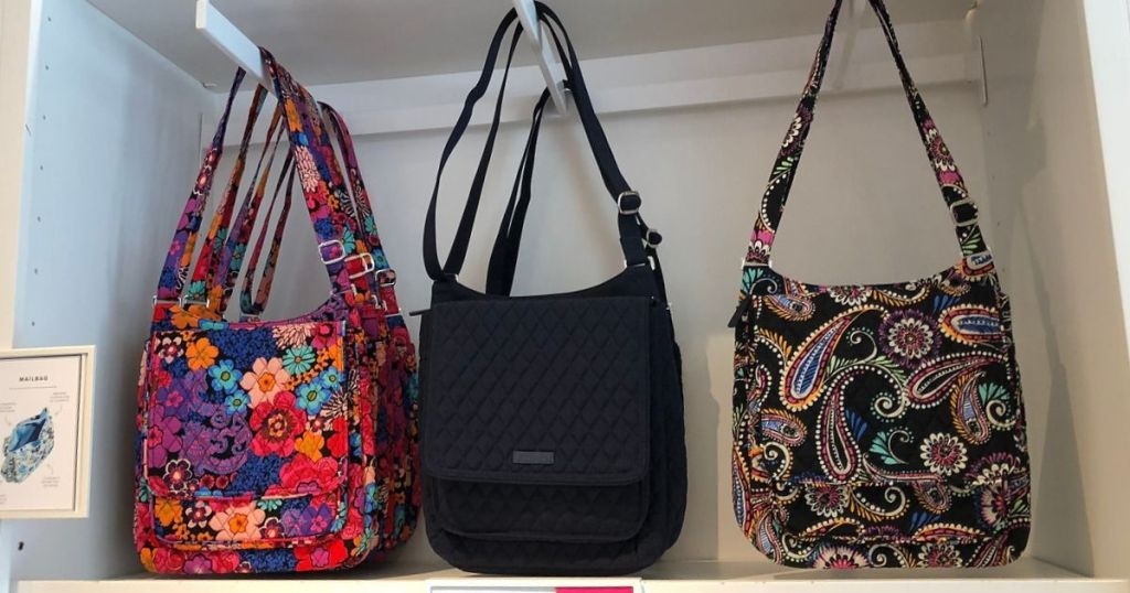 three crossbody bags hanging on a store display