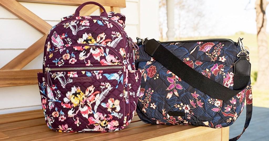 maroon floral backpack next to navy floral shoulder bag on wooden bench