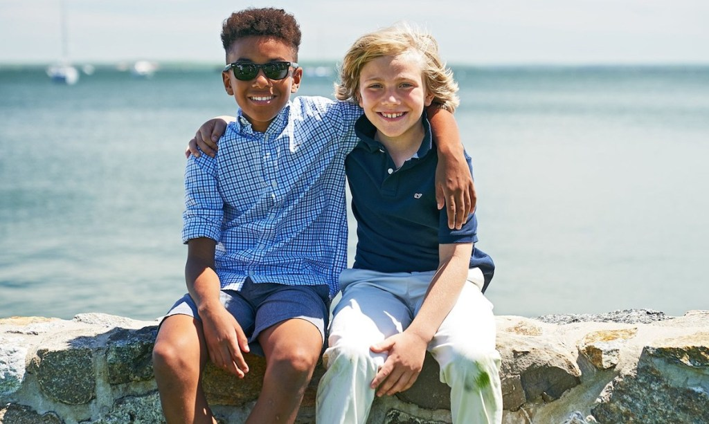 two kids sitting on a rock wall