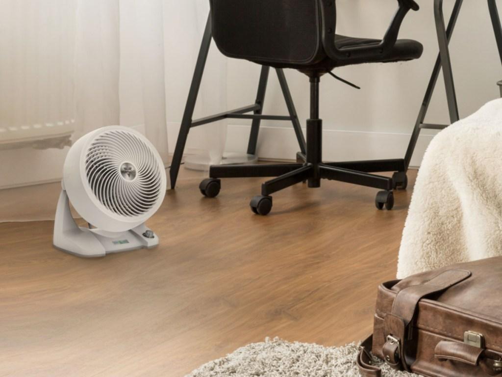 small white fan on floor near black office chair