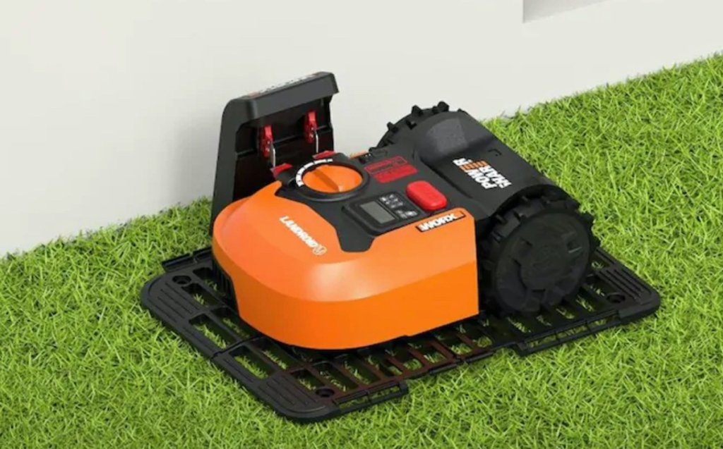 black and orange robot lawn mower trimming grass along concrete wall