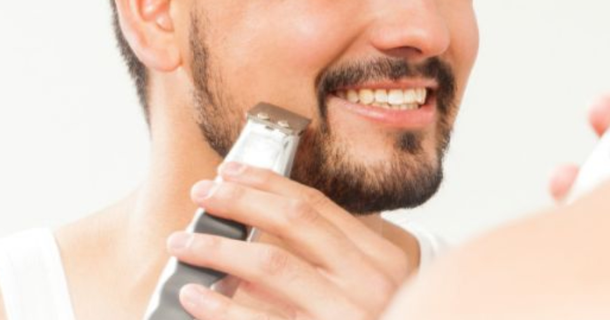 Man using a cordless trimmer to shave his face
