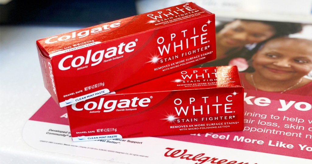 two red boxes of colgate optic white toothpaste stacked on one another on walgreens counter