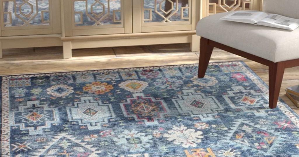 blue oriental rug on hardwood floor near grey accent table and mirrored cabinet