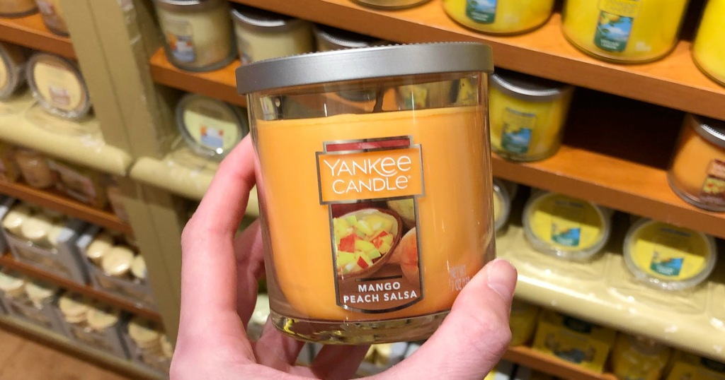 person holding up and orange yankee candle in the scent mango peach salsa