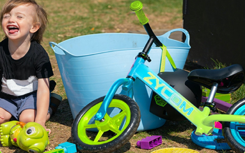 boy in grass next to toys and green and blue bike leaning against large blue bucket