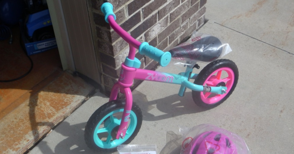 small kids pink and blue bike against brick wall outside with pink helmet in plastic on ground