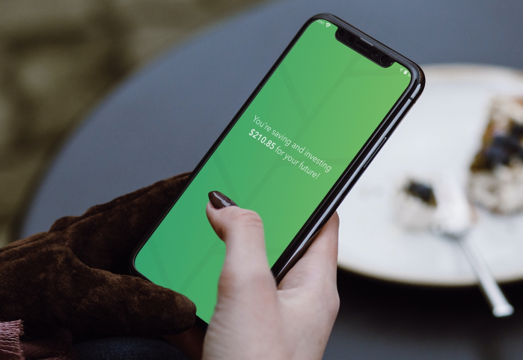 hand holding phone with green future savings on screen