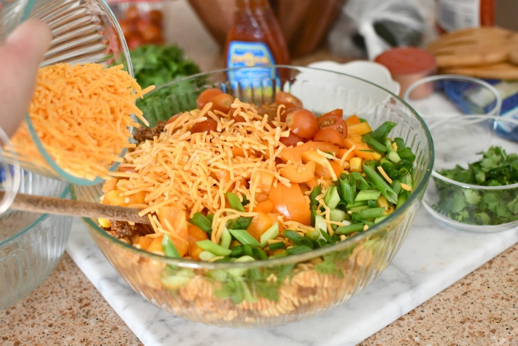 adding cheese to taco salad