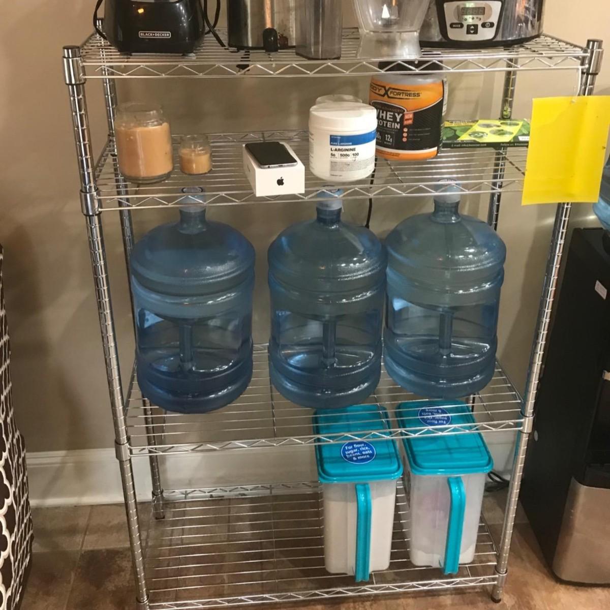 4-shelf storage unit holding large bottles of water