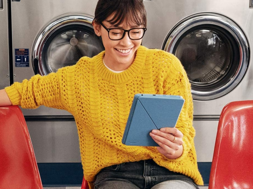 woman wearing yellow sweater looking at blue tablet in laundry mat