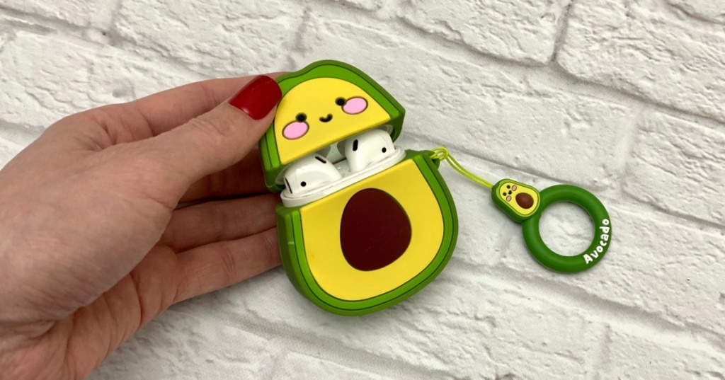 hand holding avocado Airpods case in front of white bricks