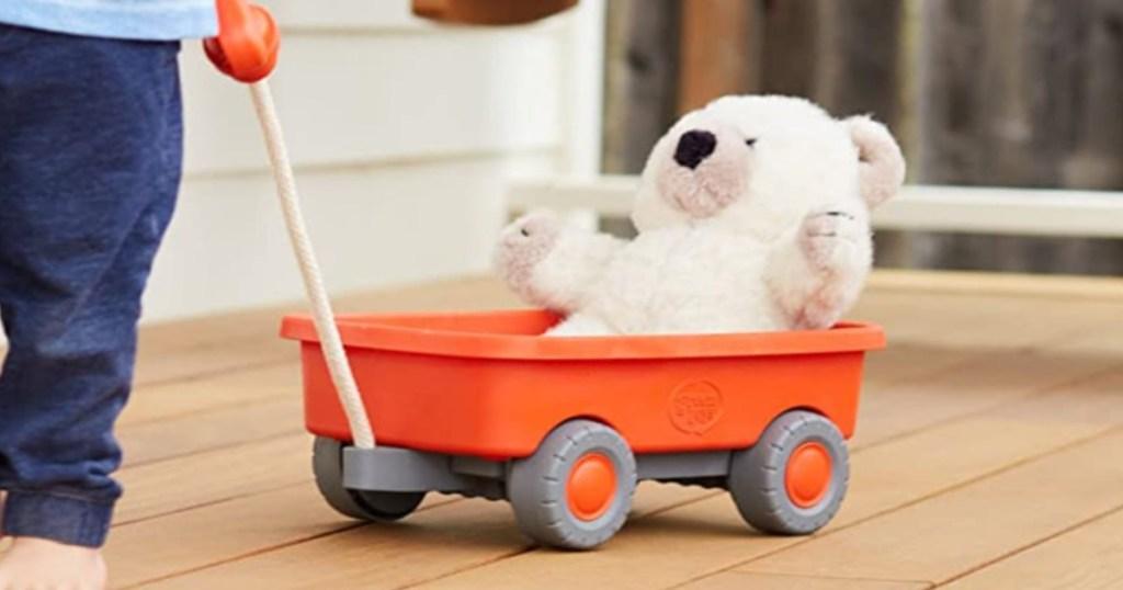 Little kid pulling orange wagon with bear in it