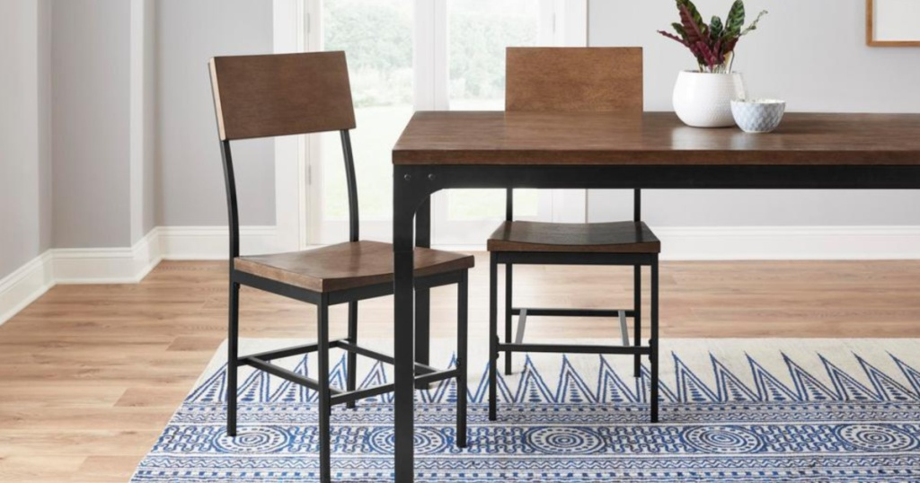 table in kitchen with 2 chairs on a rug