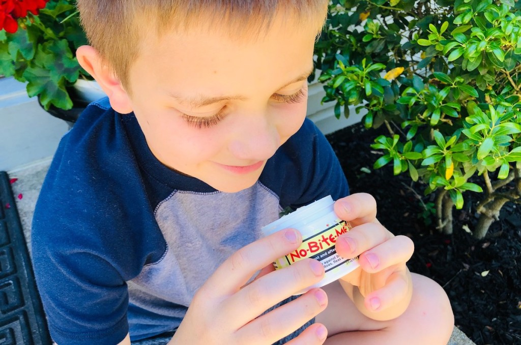 boy holding bug repellent smiling